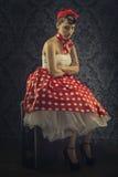 Style de vintage - femme s'asseyant dans la chambre avec la robe rouge de point de polka Image stock