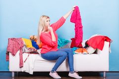 Woman looking through clothes on messy couch. Style dilemmas concept. Woman does not know what to wear sitting on messy couch with piles of clothes and looking Royalty Free Stock Photos