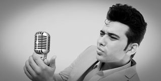 Style of Elvis Presley. A young man singing into a microphone in the style of Elvis Presley Royalty Free Stock Photography
