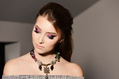 Style and fashion concept: model with colourful necklace looking down stock images