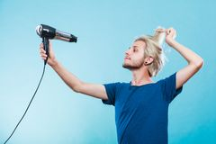 Trendy man with hair dryer Stock Images