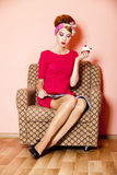 Style girl in red dress sitting in armchair Royalty Free Stock Image