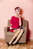 Style girl in red dress sitting in armchair Stock Photography