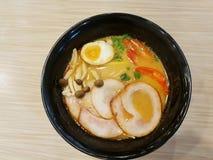 Style japonais de nourriture, vue supérieure des ramen avec la soupe à porc, à oeufs, chaude et aigre dans la cuvette noire photos stock