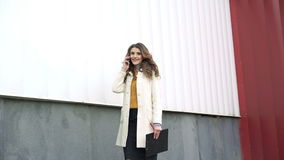 Style lady going outdoor, speaking on the phone, holding notebook and looking stock video footage