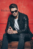 Style and masculinity. Handsome young man in sunglasses keeping hands clasped while sitting on wooden chest against red background Royalty Free Stock Photography