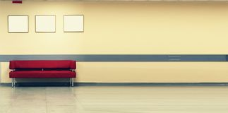 Style minimalism. Red Sofa, interior design, office. Empty waiting room with a modern red sofa in front of the door and royalty free stock photography