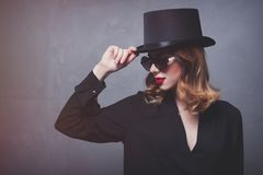 Style and mystique redhead girl in top hat and sunglasses Stock Photo