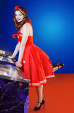 Style pinup girl in red dress, play pinball. royalty free stock images