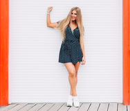 Style portrait of sexy blonde woman outdoor posing in summer. Fashion swag dressed in short dress and Fashion sneakers . Passion s Royalty Free Stock Photography