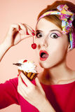 Style redhead girl with cake at pink background. Stock Photos