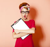 Style redhead girl in glasses and board at pink background. Royalty Free Stock Photos