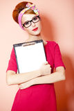 Style redhead girl in glasses and board at pink background. Stock Photo