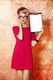Style redhead girl in glasses and board at pink background. Royalty Free Stock Photography