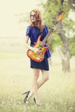 Style redhead girl with guitar at outdoor. Royalty Free Stock Image