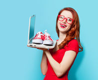 Style redhead girl with gumshoes and laptop Royalty Free Stock Photo