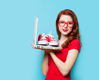 Style redhead girl with gumshoes and laptop Royalty Free Stock Photography