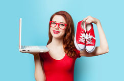 Style redhead girl with gumshoes and laptop Stock Photos