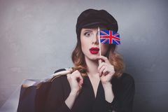 Girl in hat with shopping bags and flag of United Kingdom Royalty Free Stock Image