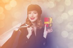 Style redhead girl in hat with shopping bags and gift box Royalty Free Stock Photography