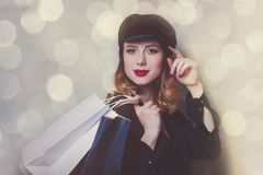 Style redhead girl in hat with shopping bags Royalty Free Stock Photos