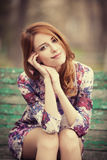 Style redhead girl sitting on the bench Stock Images