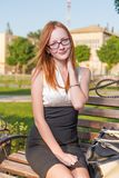 Style redhead girl sitting on the bench Royalty Free Stock Image