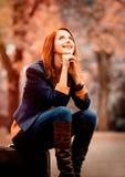 Style redhead girl with suitcase. Sitting on autumn season park royalty free stock photo