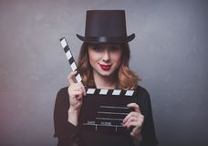 Style redhead girl in top hat with movie clapperboard Stock Images