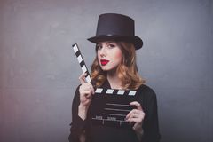 Style redhead girl in top hat with movie clapperboard Royalty Free Stock Photography