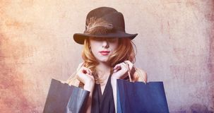 Style redhead woman in hat with feather holding shopping bags Royalty Free Stock Image