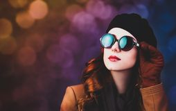 Style redhead woman in sunglasses and coat. On gray background stock images