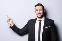 Style and smile. Portrait of confident young man in formalwear looking at camera and pointing away while standing against grey background Stock Photos