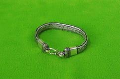 Style steel bracelet. On green velvet background Stock Photos