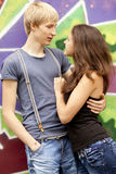 Style teen couple near graffiti background. Royalty Free Stock Photo