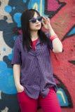 Style teen girl standing near graffiti wall. Royalty Free Stock Photography