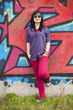 Style teen girl standing near graffiti wall. Royalty Free Stock Photos
