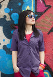 Style teen girl standing near graffiti wall. Royalty Free Stock Images