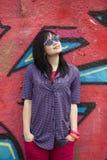 Style teen girl standing near graffiti wall. Stock Photography