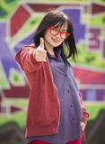 Style teen girl standing near graffiti wall. Royalty Free Stock Photos