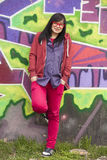 Style teen girl standing near graffiti wall. Stock Photos