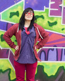 Style teen girl standing near graffiti wall. Royalty Free Stock Image
