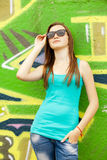 Style teen girl in sunglasses near graffiti background. Stock Images