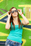 Style teen girl in sunglasses near graffiti background. Stock Photos