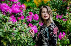 Style woman near rhododendron flowers in a grarden stock image