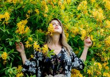 Style woman near yellow flowers in a grarden stock photos
