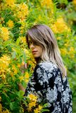 Style woman near yellow flowers in a grarden royalty free stock photography