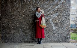 Style woman in red coat and net bag waking home after shopping. Eastern Europe stock photography