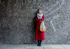 Style woman in red coat and net bag waking home after shopping. Eastern Europe stock photo