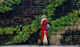 Style woman in red coat and net bag waking home after shopping. Eastern Europe royalty free stock image